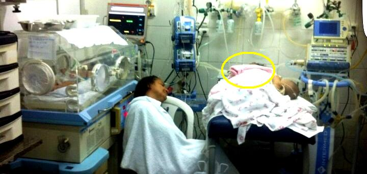 O círculo amarelo mostra a bolsa rosa como única proteção da criança, enquanto a mãe adormece em uma cadeira qualquer...