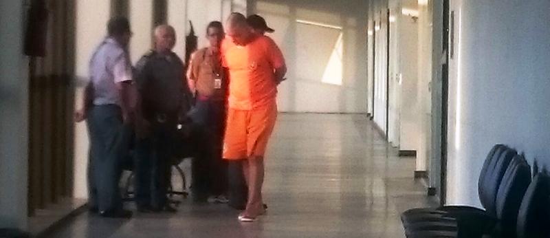 Lucas Porto aguardando a audiência de custódia, já com a cabeça raspada e com roupa de presidiário